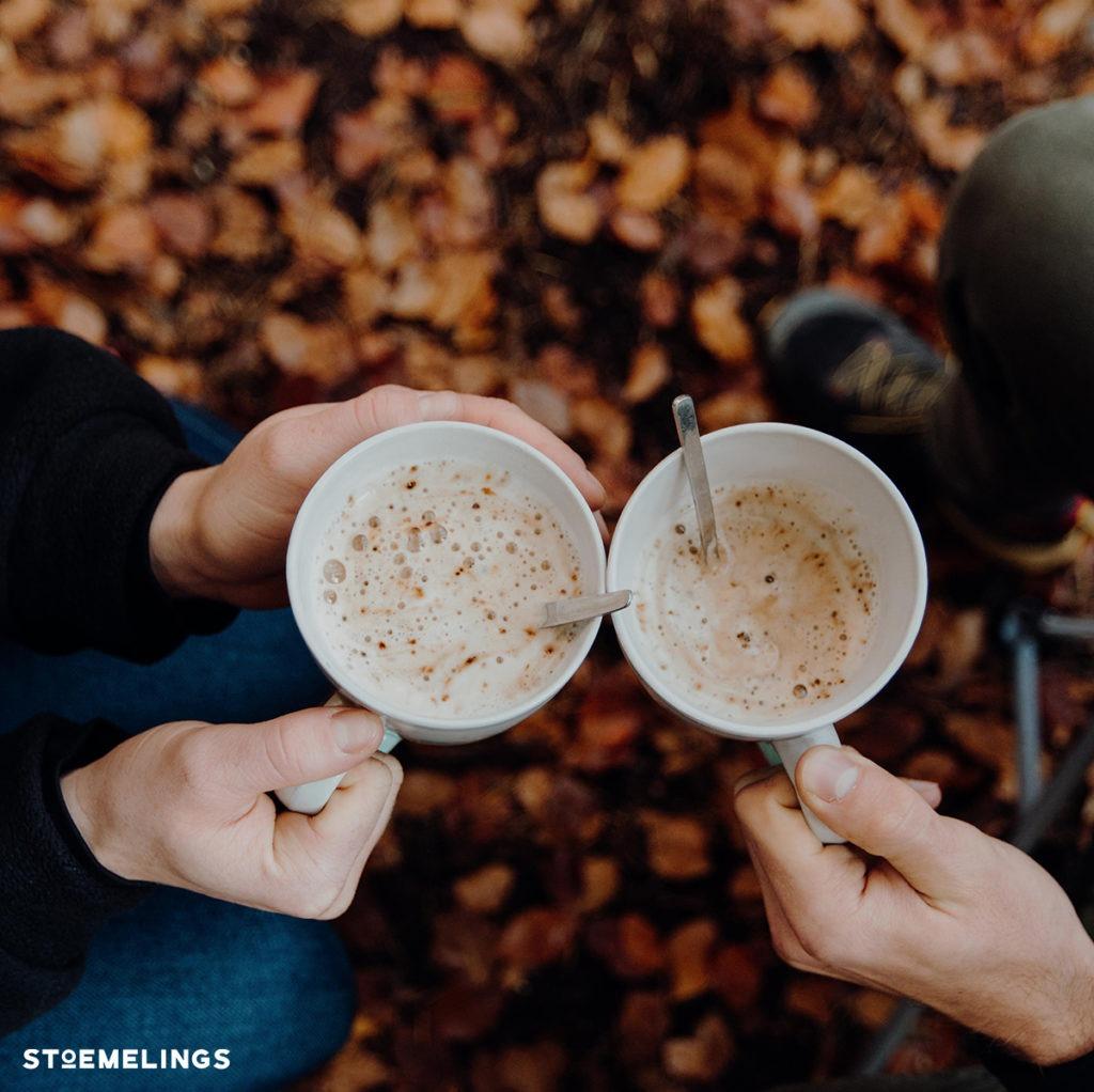 Deux clients stoemelings qui boivent une tasse de café dans un bois lors d'un trip en tente de toit