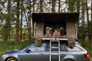 deux enfants dans une tente de toit sur une voiture qui s'amusent comme des petits fous