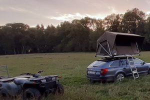 tente de toit dans prairie avec quad