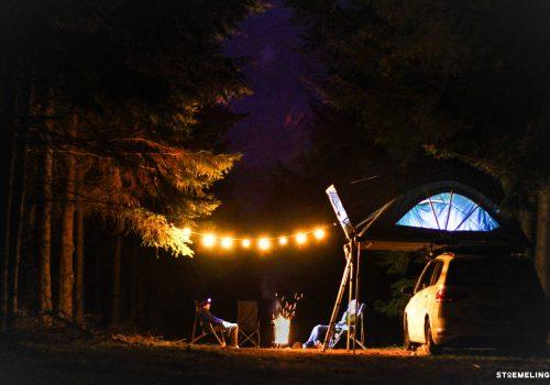 camping de nuit avec une tente de toit 4 places familiale en foret avec une guirlande et un feu dans un brasero stoemelings