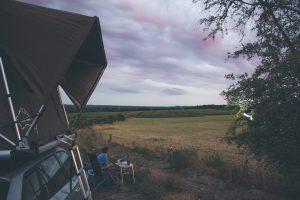 coucher de soleil sur champs avec tente de toit jimba