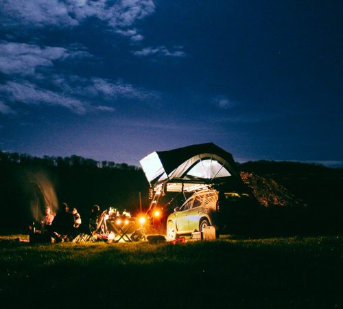 Tente de toit familiale dans une prairie autour du feu